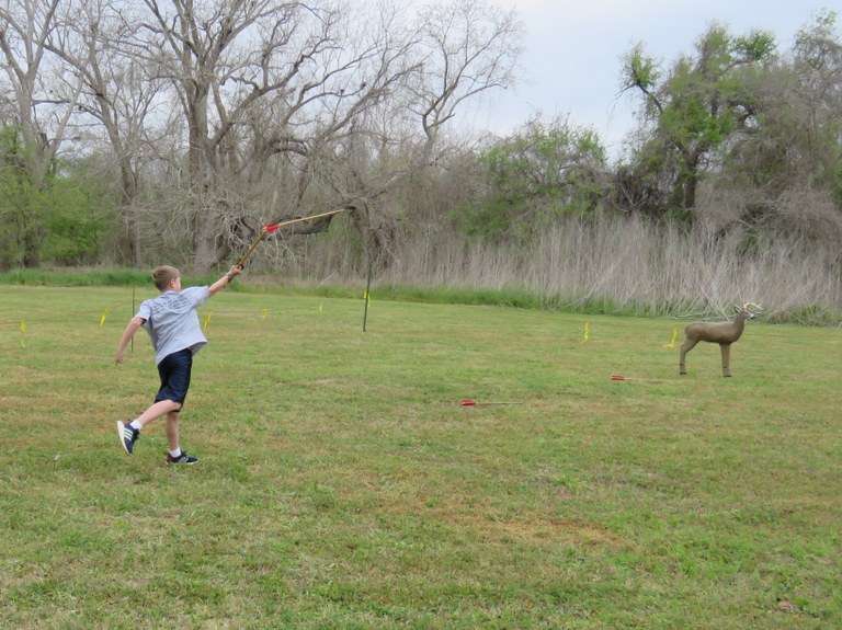 Boy throwing dart with atlatl