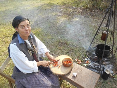 Women dressed in period clothing preparing a meal.