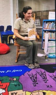 A park ranger reading a children's story