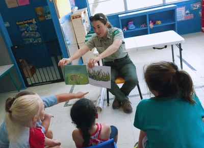 Ranger Amy is showing a group of children illustrations for a children's book.