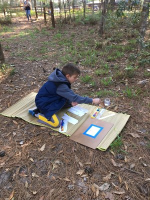 Young boy watercoloring outside.