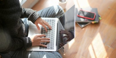 Person sitting on floor typing on laptop