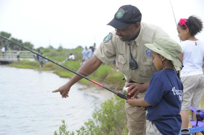 Game Warden teaching child to fish