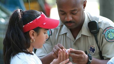Game Warden helping a child fish