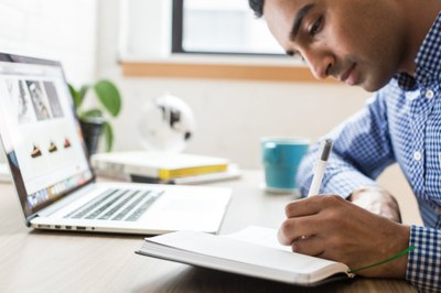 Man writing notes in front of laptop
