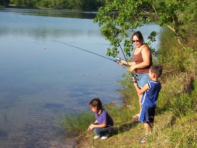 Family holding fishing poles on the edge of a lake