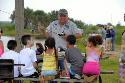 adult male volunteer teaching youth how to use a fishing rod-n-reel