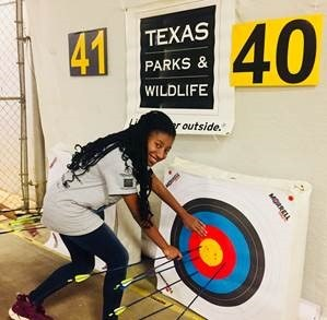 NASP archer retrieves her arrows from target