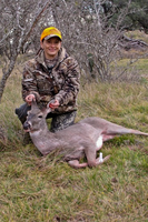 Hunter posing with harvested deer