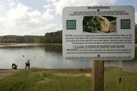 Sign at lake warning of Giant Salvinia