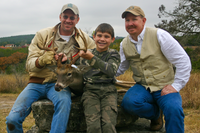 Young hunter and two adults with harvested deer