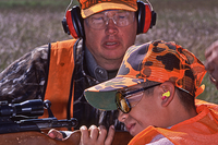 Adult instructing young hunter on shooting