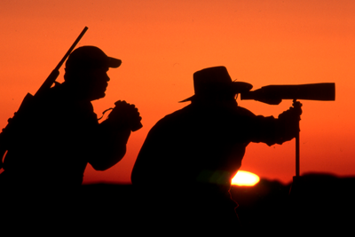 hunters using spotting scope looking for game as the sun sets