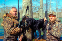 duck hunters in timber camo with dog