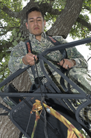 Hunter using haul line to up bow to tree stand