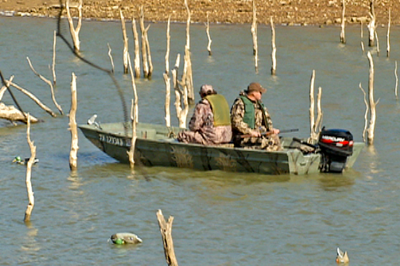 Hunters sitting towards back of boat