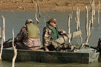 hunters in boat with guns in cases