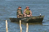 hunters in boat wearing PFD's