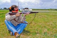 Shooter sitting cross-legged