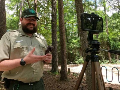 Park ranger recording a program on a tablet on a tripod under tall trees.