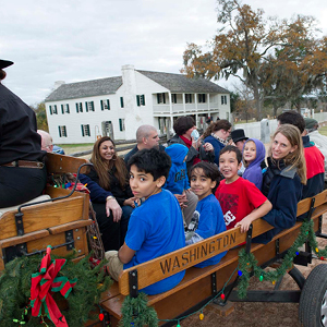 Children and parents riding in wagon at historic site