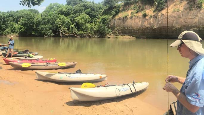 kayaks parked on red sand beach, bluff across river