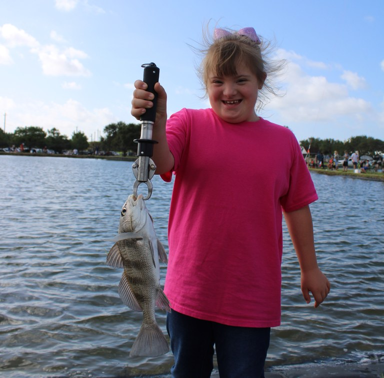 A little girl has caught a fish