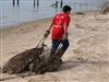 Volunteer Dragging Abandoned Crab Traps Onto Beach, San Antonio Bay, 2-19-11