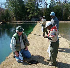 Instructor helps scouts with fly rods in hatchery pond.