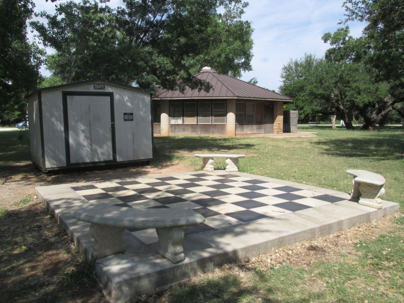 Outdoor chess/checkers board next to group hall.