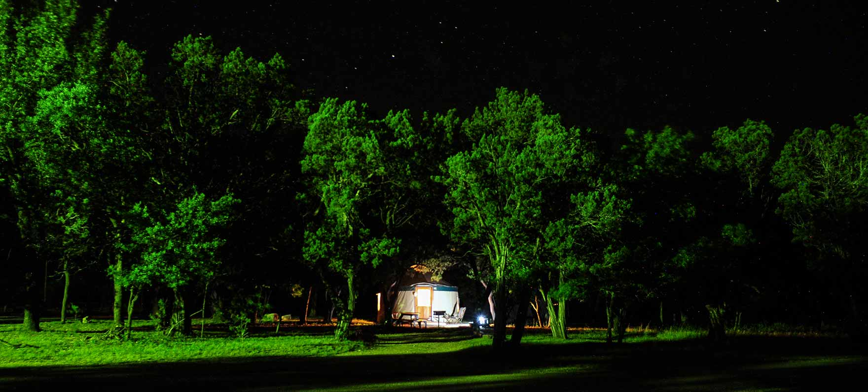 The yurt at night. Thick canopies of native pecans, red oaks and willows cover paths where white-tailed deer roam free.