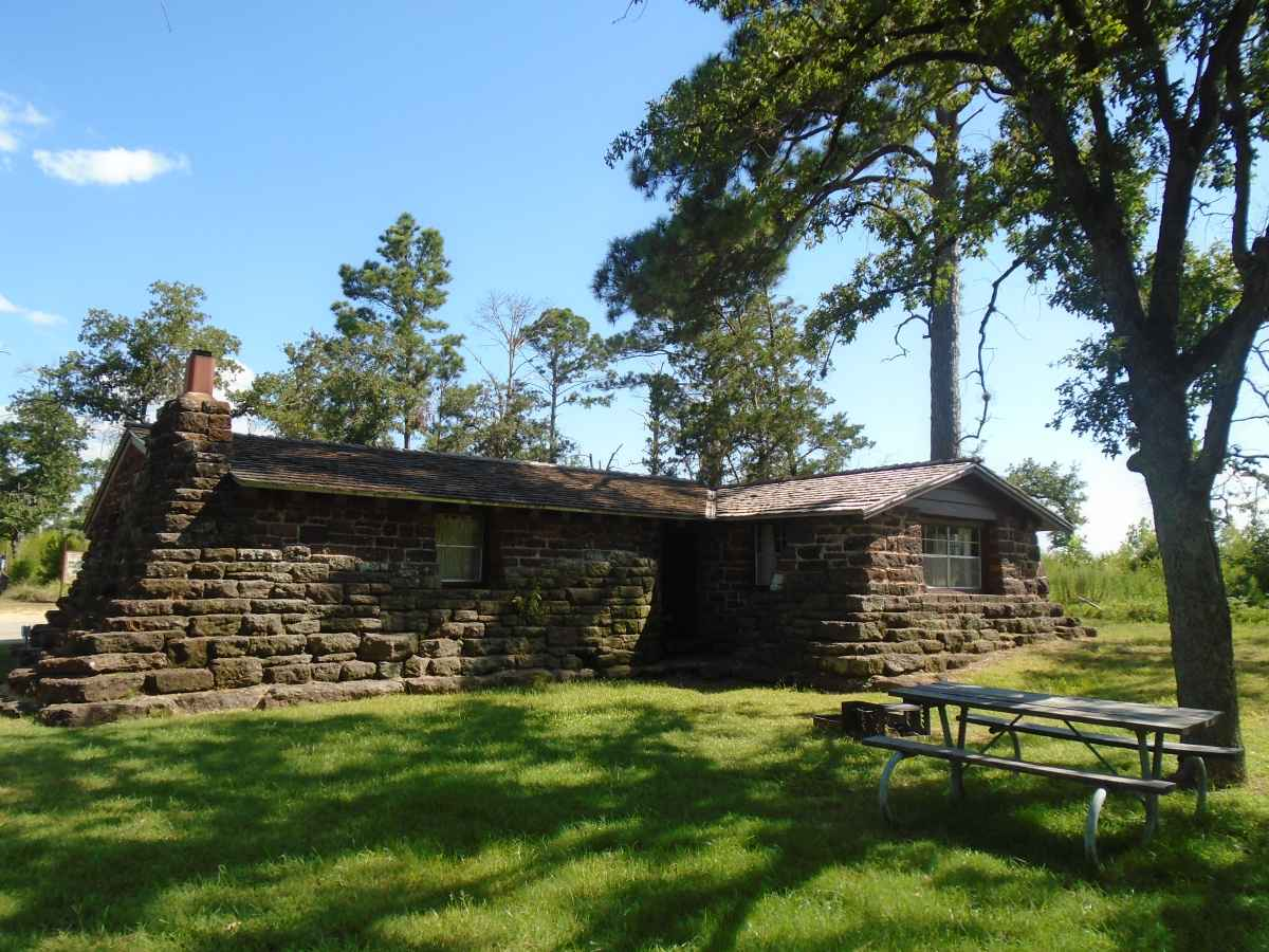 A picnic table and a fire ring with a grill are in back of Cabin 14.