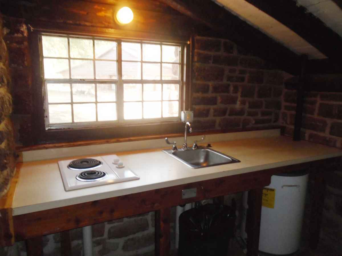 There is a microwave, a small refrigerator, a sink and a 2-burner stove in the kitchen area of Cabin 4.