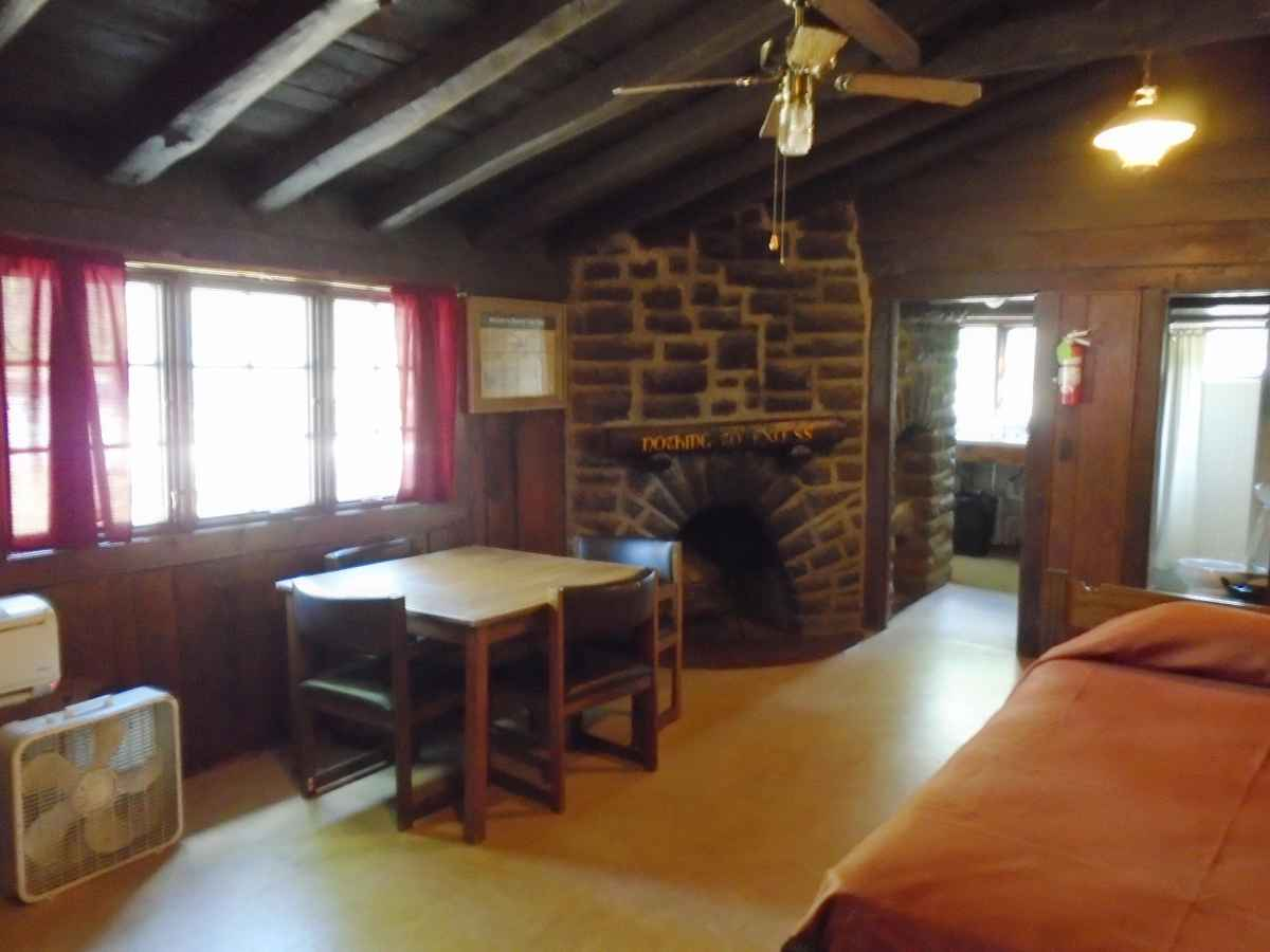 The living area of Cabin 6 has a single bed, fireplace and a table with chairs.