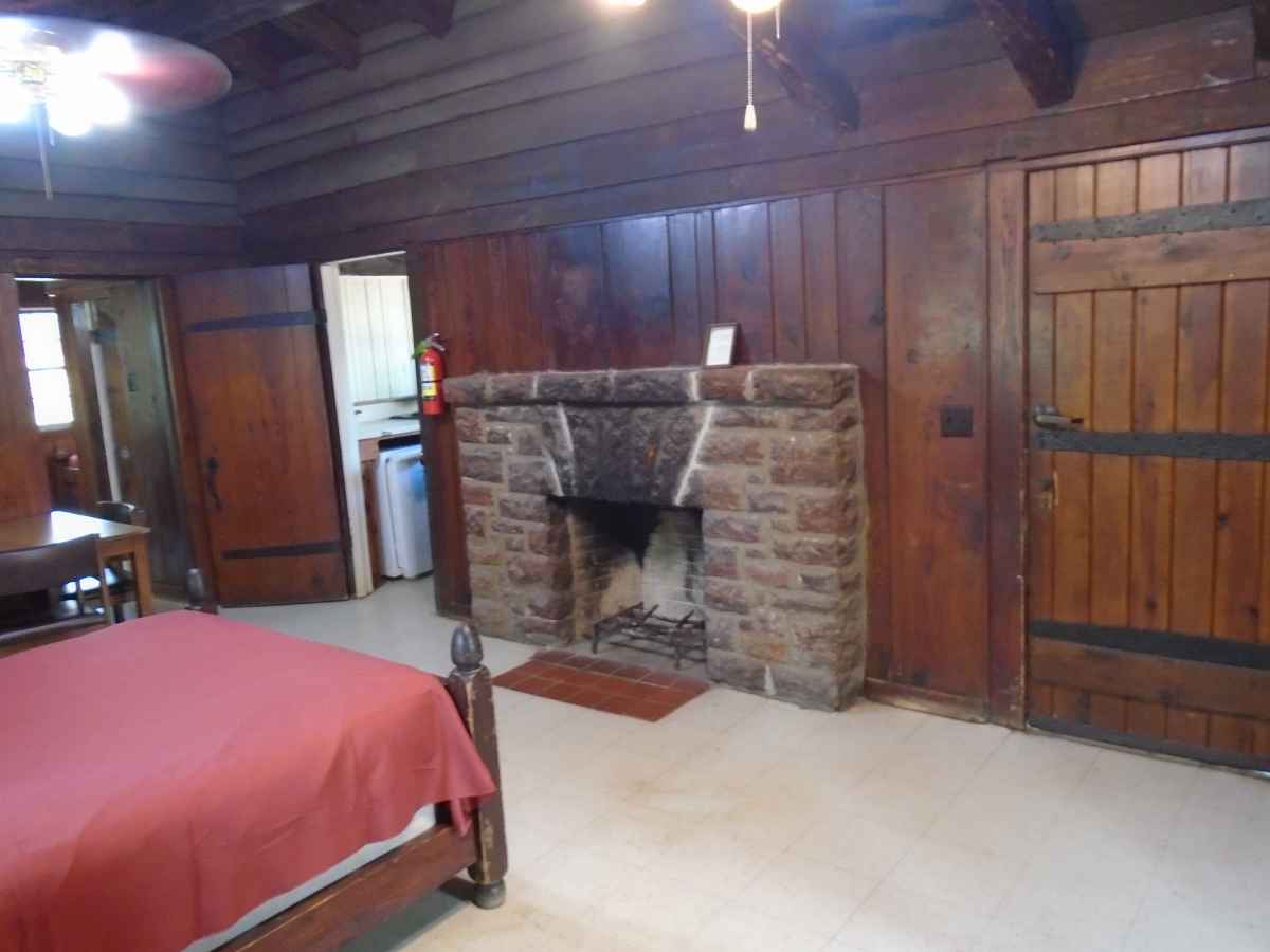 The living area of Cabin 7 has a double bed, a table with chairs and a fireplace.