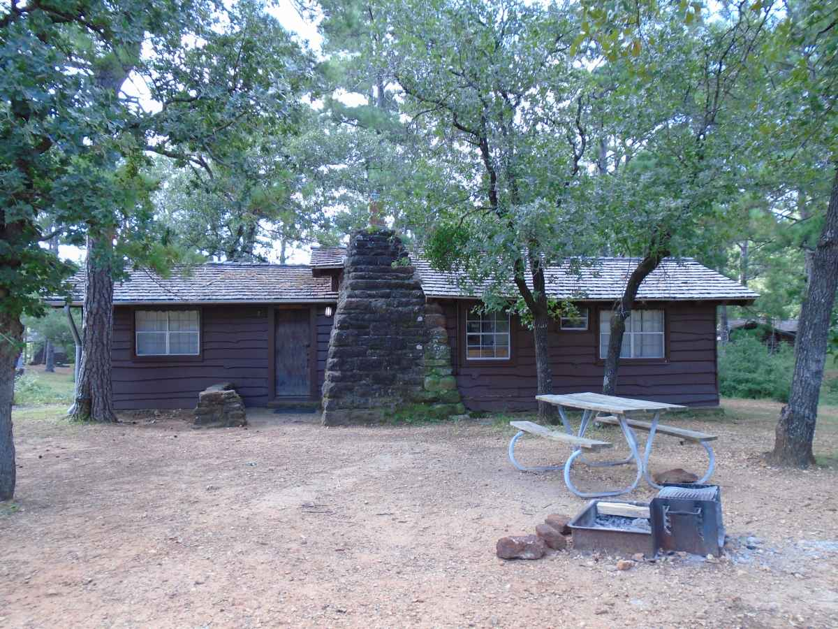 There is a picnic table and a fire ring with a grill in front of Cabin 7.