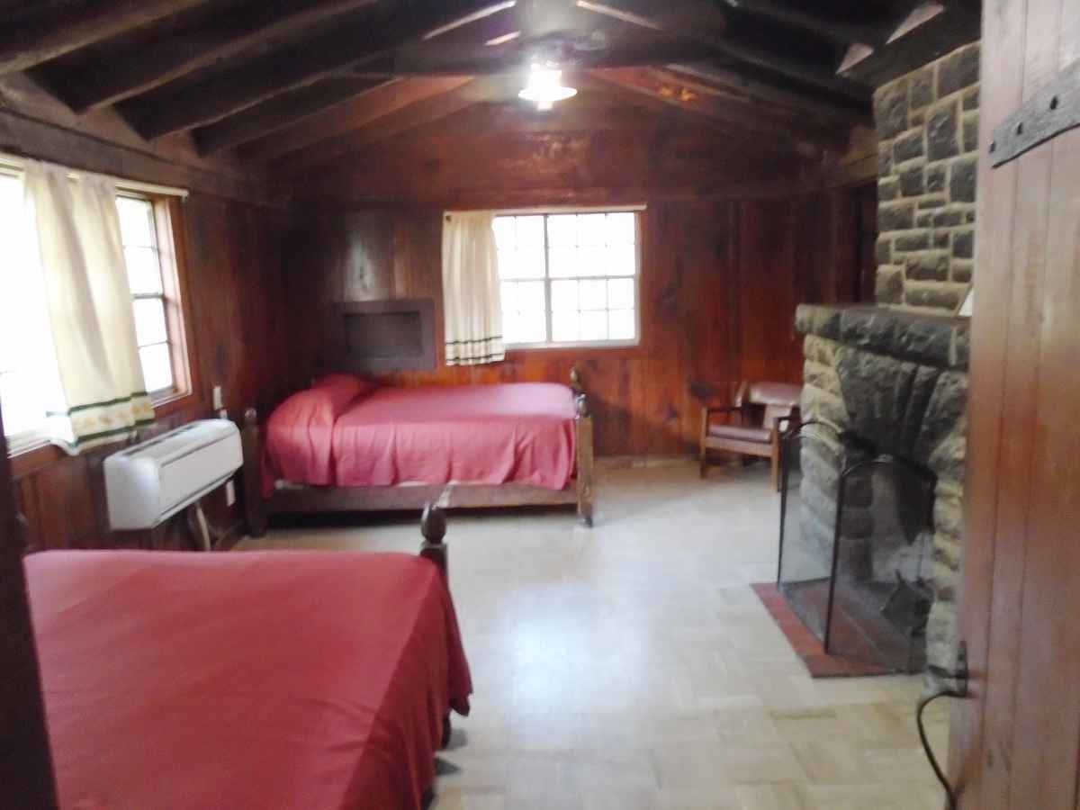 The living area of Cabin 9 has Two double beds and a fireplace.