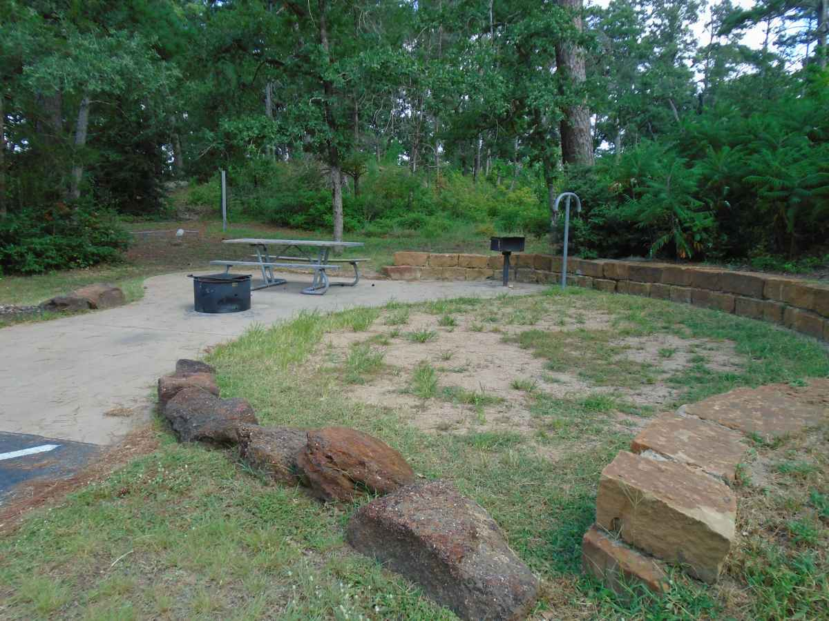 Accessible Campsite #61 has a raised fire ring, upright grill, lantern post, picnic table and paved walkways designed for use with a wheelchair.