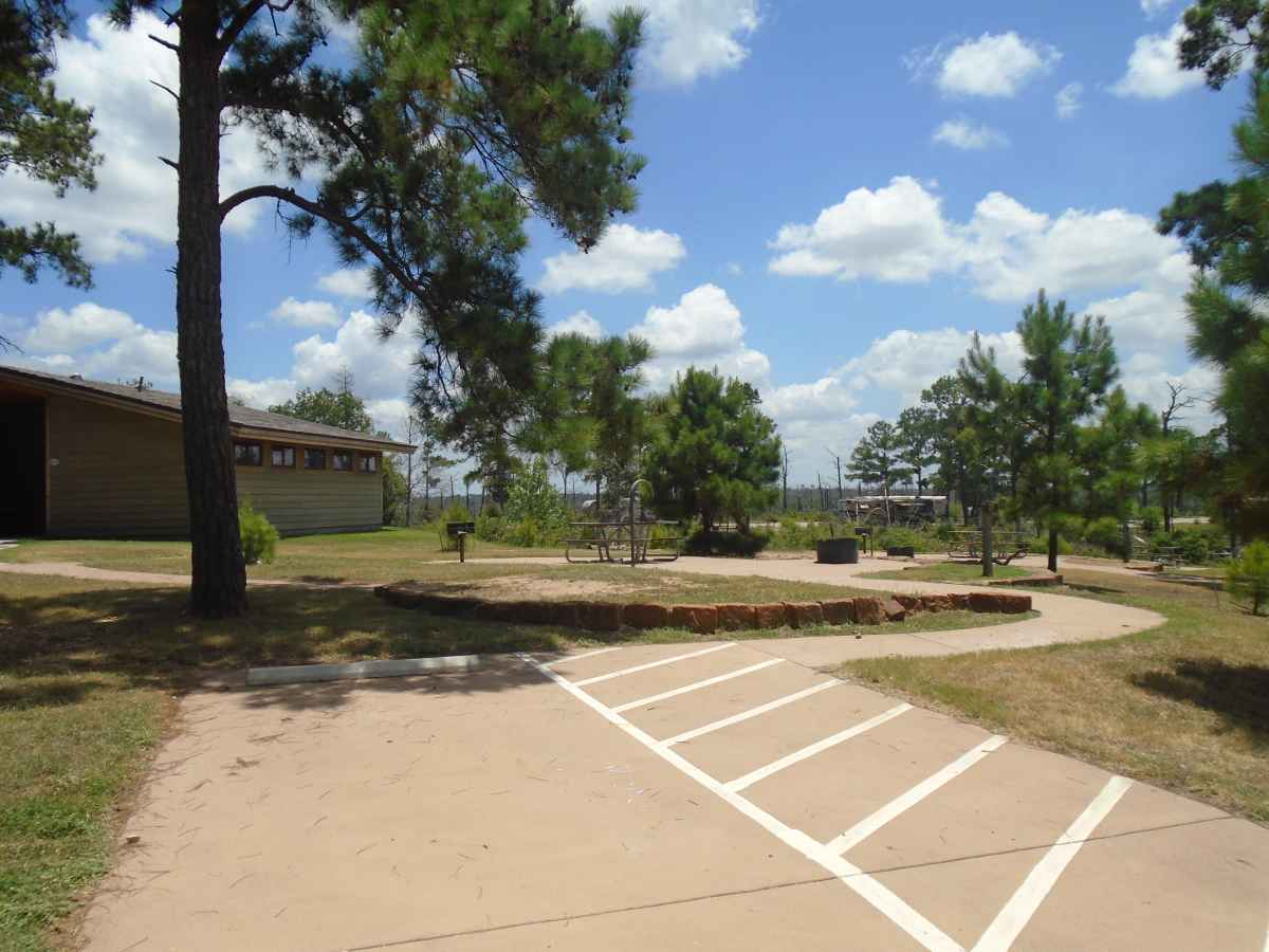 Accessible Campsite #27 is close to the bathrooms and has a raised fire ring, upright grill, lantern post, picnic table and paved walkways designed for use with a wheelchair.