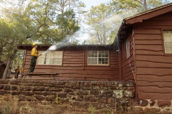 Firefighter standing on picnic table spraying roof of CCC cabin