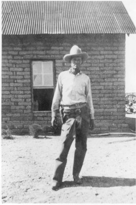 Black & white photo of a rancher in front of buildings