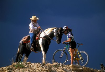 Horseback rider and bicyclist conferring on the trail.
