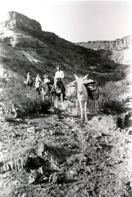 historic image of people riding on horses in the desert