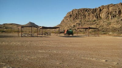 Campsite with picnic tables and shade shelters