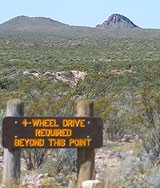"""view of desert with sign that says """"Four-wheel drive required beyond this point."""""""