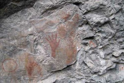 red hand prints on a rock face