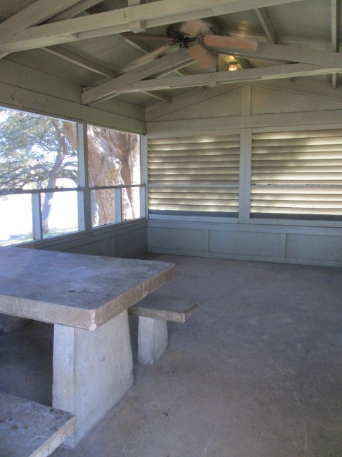 Inside a screened shelter is a picnic table, light and a ceiling fan.