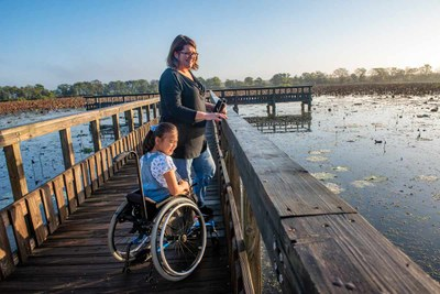Girl using a wheelchair on a boardwalk with Mom next to her
