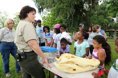 Group of kids talking with park ranger and looking at artifacts