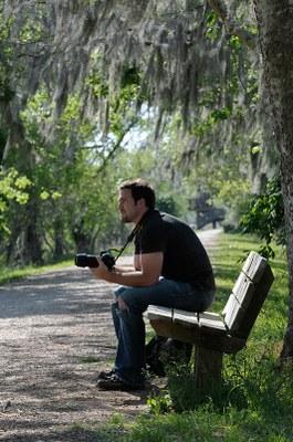 Guy sitting on bench holding camera